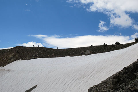 hikers crossing ridge above snow bank