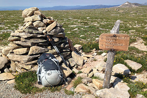 Junction trail sign near large cairn on Flattop Mountain. A pack and poles lay against the cairn.