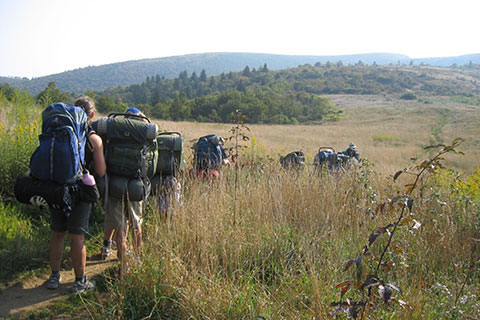 students backpacking through tall grass