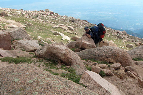 Hiker carrying two packs struggling on the upper slopes of Pikes Peak
